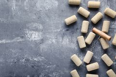 Wine corks with corkscrew. On grey wooden table stock photography