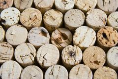 Wine corks in horizontal stacked arrangement. Colorful natural nork bottle stoppers. Some showing damage and holes from corkscrew Stock Photos