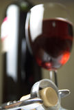 Wine and corkscrew. Bottle and glass of red wine with corkscrew in foreground stock images