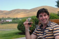 Wine Country 3. A man enjoys a glass of red wine in a hilly outdoor wine country setting Stock Image