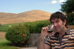 Wine Country 4. A man enjoys a glass of red wine in a hilly outdoor wine country setting Royalty Free Stock Image