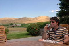 Wine Country 5. A man enjoys a glass of red wine in a hilly outdoor wine country setting Royalty Free Stock Image