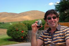 Wine Country. A man enjoys a glass of red wine in a hilly outdoor wine country setting Stock Photography