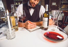 Wine critic is in good mood. Smiling man is sitting at table and writing wine critics Royalty Free Stock Image