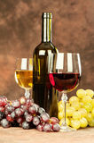 Wine cups and grape. Cup of a red wine in front of grape, bottle and glass of white wine Royalty Free Stock Images