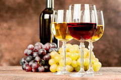 Wine cups and grape. Cups of red and white wine in front of grape and bottle Royalty Free Stock Image