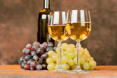 Wine cups and grape. Cups of white wine in front of grape and bottle Royalty Free Stock Photo