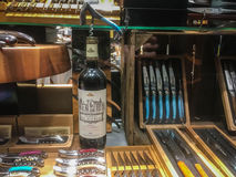 Wine and cutlery store display, Paris, France. Bottle of red wine and assorted cutlery and wine openers on display in lighted shop window in Paris, France royalty free stock photos