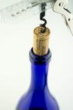 Vin dans la bouteille bleue avec le tire-bouchon d'isolement Photos stock
