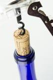 Vin dans la bouteille bleue avec le tire-bouchon d'isolement Photographie stock