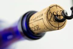 Vin dans la bouteille bleue avec le tire-bouchon d'isolement Photos libres de droits