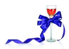Wine dans le verre à vin et la proue bleue de cadeau de satin, d'isolement sur le blanc Photos stock