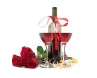 Wine dans les verres, les roses rouges et le ruban d'isolement sur le blanc Photographie stock libre de droits