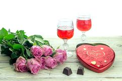 Wine dans les verres, les roses et une boîte de bonbons sur une table en bois Images libres de droits