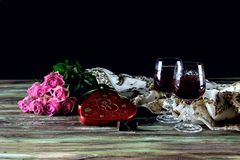 Wine dans les verres, les roses et une boîte de bonbons sur une table en bois Photographie stock