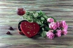 Wine dans un verre, des roses et une boîte de chocolats sur une table en bois Photographie stock