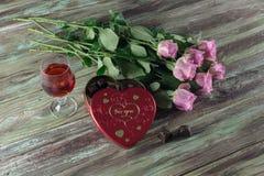 Wine dans un verre, des roses et une boîte de chocolats sur une table en bois Images libres de droits