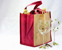 Wine Date. Canvas wine satchel with 4 bottles of wine, two crystal wine goblets and cork screw.  Presented on plain white background Stock Photos