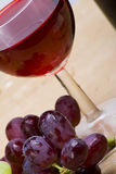 Wine detail. A stylish angled view of fresh grapes with a glass of red wine Stock Images