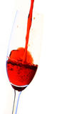 Wine and dine. Red wine being poured in champagne flute against white background Royalty Free Stock Photos