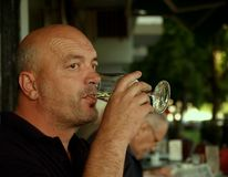 Wine Drinker. Adult man finishing glass of white wine on the small caffe terrace Royalty Free Stock Photo