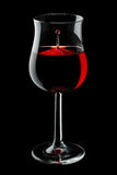 Wine drop. A wine drop in a glass of red wine,  on black background Royalty Free Stock Image