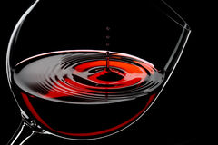 Wine drops. Glass of red wine, drops in motion, studio shot