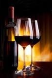 Wine durch das Glas gegen den Kamin mit Feuer Lizenzfreie Stockbilder