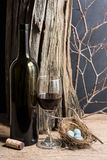 Wine and egg. Still life photography : red wine in bottle and glass with egg in nest , tree stump and branch in easter concept stock photography