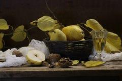 Wine en una copa transparente y peras en una cesta wattled Fotos de archivo libres de regalías