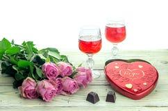 Wine en vidrios, rosas y una caja de dulces en una tabla de madera Imágenes de archivo libres de regalías