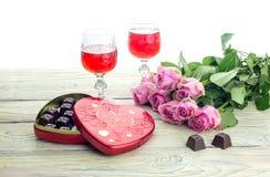 Wine en vidrios, rosas y una caja de dulces en una tabla de madera Foto de archivo