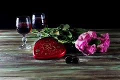 Wine en vidrios, rosas y una caja de dulces en una tabla de madera Fotos de archivo
