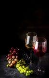 Wine en vidrios y diversos tipos de uva en fondo oscuro imágenes de archivo libres de regalías