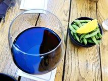 Wine en vin rouge en verre de tache floue de mouvement de foyer sélectif dans un verre Vin avec les pois et le citron Images stock