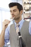 Wine-expert in work. Wine-taster smelling cork eyes closed after opening bottle of wine Royalty Free Stock Photo