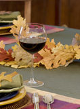 Wine, fall table - vertical. Casual fall table setting with focus on red wine in glass royalty free stock photos