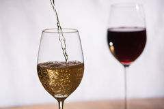 Wine filled into a glass. Wine gets filled into a glass stock photography