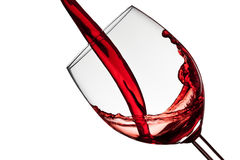 Wine fills a wineglass. On a white background Royalty Free Stock Photography