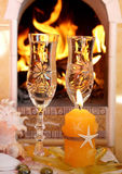 Wine and fire. Still-life with glasses of white wine and sea shells against burning fireplace Stock Images