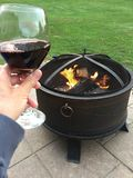 Wine by the fire. Fire pit on patio Stock Photo