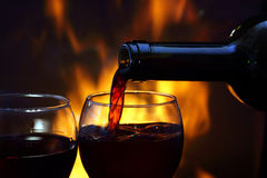 Wine by the fireplace. Pouring wine by the fireplace Royalty Free Stock Photography