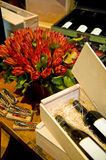 Wine and flowers. Composition of some wine bottles in wooden boxes with a bunch of red flowers royalty free stock image