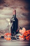 Wine of flowers and candles on the table. Red wine bottle, two glasses of wine, rose with decoration by red hearts on wooden table. Valentines day celebration Stock Image