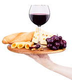 Wine and food with waiter hand. Waiter hand with wooden board including a wine,bread,cheese and grapes Royalty Free Stock Photo