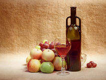 Wine and fruit against brown sacking Royalty Free Stock Image