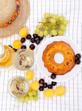 Wine, fruits and cake on a tablecloth Royalty Free Stock Images