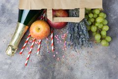 Wine, fruits, flowers set for the party or picnic in a paper craft pack on a gray concrete background. Top view. Copy space below. Festive, joyful mood stock image