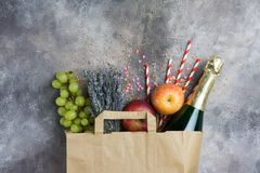 Wine, fruits, flowers set for the party or picnic in a paper craft pack on a gray concrete background. Top view. Copy space on top. Festive, joyful mood stock photos