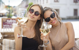 Wine fun with friends. Portrait of two young beautiful women having some wine Royalty Free Stock Photography